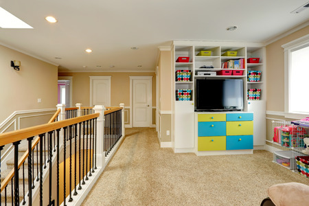 units: Upper level of modern house furnished with built-in cabinets, tv, storage units  View of staircase and railings