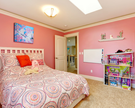 Gentle girls bedroom with white bed and pink walls  View of board on the wall and toy house