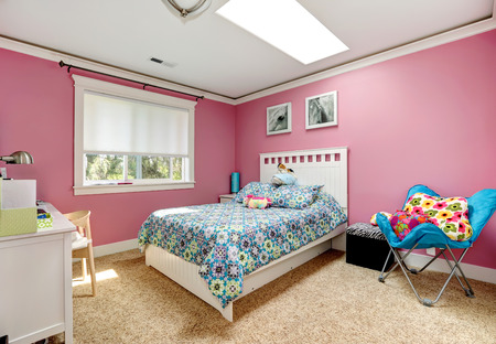 Gentle girls bedroom with white bed and pink walls  View of bed with blue bedding,blue chair photo