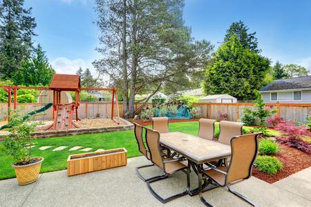 Achtertuin met terras en een speeltuin voor kinderen