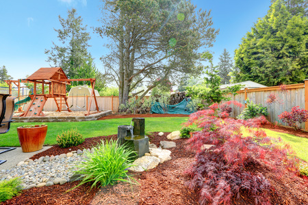 Fenced backyar with well designed flower bed and play yard for kids photo