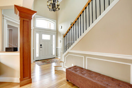 Luxury home interior  View of entrance door, stairs with iron and wood railings and ottoman  photo