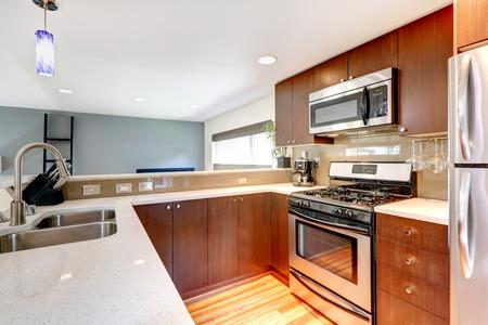 estufa: Pequeña cocina en un apartamento moderno Vista de gabinetes, estufa y microondas de acero