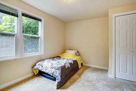 Small bedroom with window, carpet floor  View of mattress covered with floral bedding photo