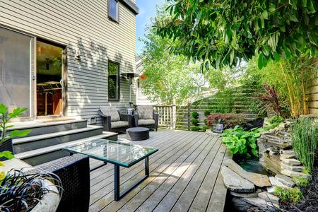 Mooie zomer achtertuin met exotische landschap. Uitzicht op rieten stoelen met Ottaman en glazen tafel