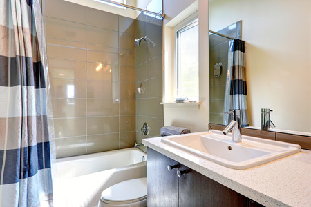 bathroom wall: Small bathroom with window.  View of washbasin cabinet with mirror and tub with tile wall trim
