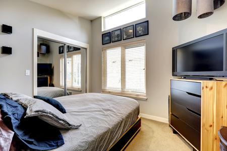 closet door: Small bedroom with mirror door closet, single bed and TV