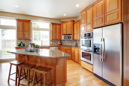 kitchen cabinets: Kitchen room with wooden cabinets, steel appliances, island and stools. Stock Photo