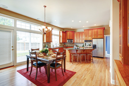 back kitchen: Modern kitchen with steel appliances and island. View of served dining table set on a red rug