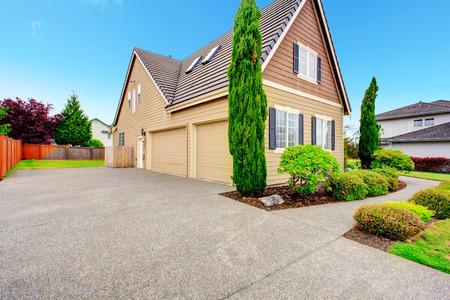 Clapboard gevelbeplating huis met twee auto garage en oprit. Viw van groene beautitul landschap