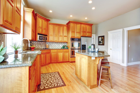 back kitchen: Kitchen room with wooden cabinets, steel appliances, island and stools. Stock Photo