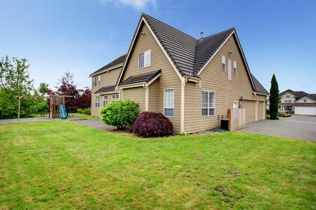 Big house with backyard playground, green lawn, garage and driveway photo