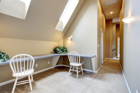 upstairs: Upstairs hallway with attached to the wall counter tops, white chairs and velux windows Stock Photo
