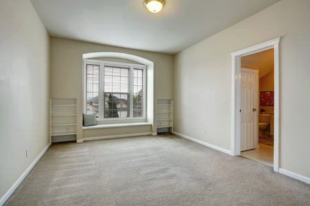 Empty bedroom with open door to bathroom  View of arch window with bench and built-in shelves photo