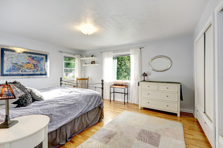 Light grey bedroom with hardwood floor and old rug  View of white antique cabinet, iron frame bed photo