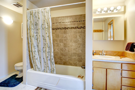 trim wall: View of bath tub with curtains and tile trim wall, vanity with mirror and toilet with blue rug