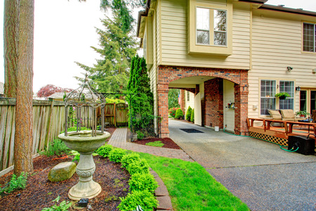 Beautiful backyard view. Brick archway, flower bed with antique concrete fountain. photo