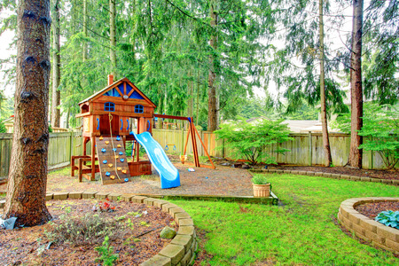 fenced: Fenced green backyard with playground for kids Stock Photo
