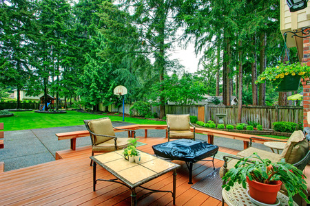 Backyard patio area with antique table set and fire pit  View of basketball court and green lawn