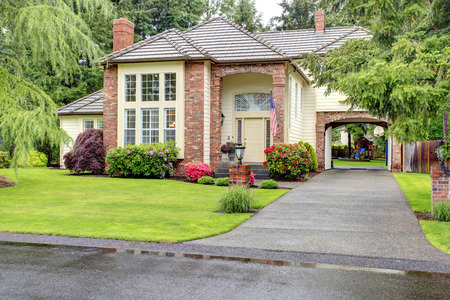 Beautiful curb appeal  Large brick house with siding trim and tile roof  View of entrance hight ceiling porch and driveway with arch photo