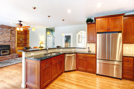 kitchen cabinets: Kitchen wooden cabinets with steel appliances  View of brick fireplace Stock Photo