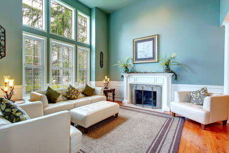 area: High ceiling aqua living room with white leather couch, ottaman, armchairs and fireplace Stock Photo