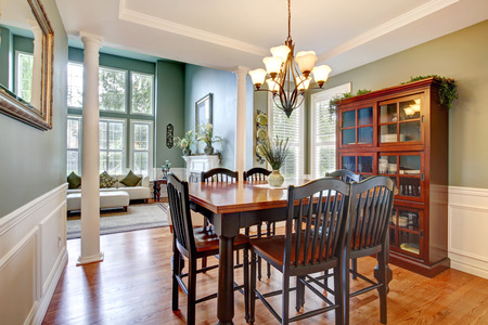 Luxury house with high ceiling and columns  Dining room with storage cabinet and dining table set photo