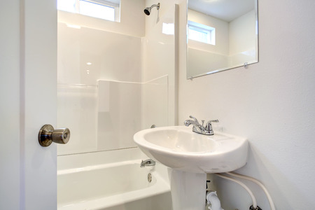 Small bathroom with washbasin stand, mirror and tub