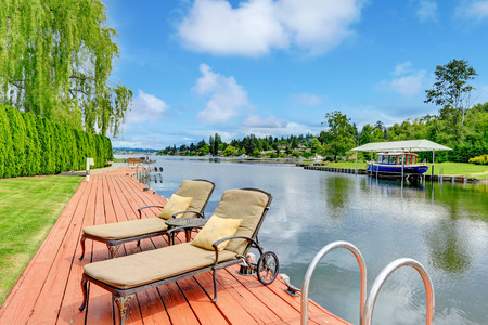 Amazing backyard view. Private dock with two antique deck chairs and table photo
