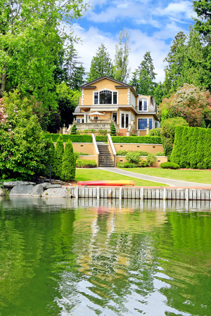 american house: Amazing luxury house with beautiful landscape and private dock. View from the boat Stock Photo