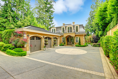 Luxury house with beautiful curb appeal. View of three car garage and driveway photo
