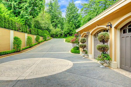 american house: Beautiful driveway with three car garage. View of pots with trees and trimmed hedges