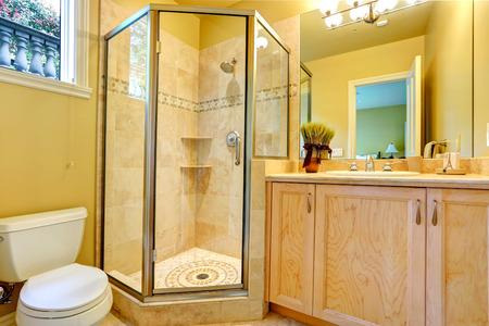 bathroom mirror: Cozy bathroom with toilet, glass door shower and wooden vanity with mirror