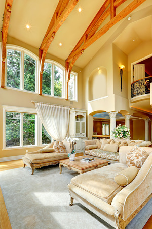light columns: Impressive living room with high ceiling, antique furniture, columns and balcony