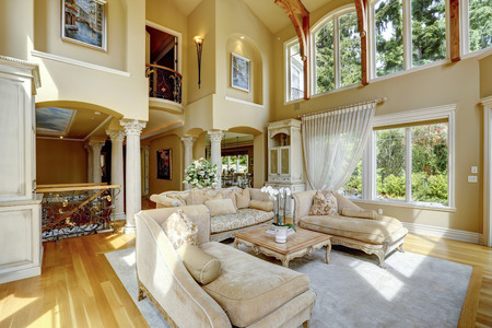 light columns: Impressive high ceiling living room with antique furniture, columns and balcony Stock Photo