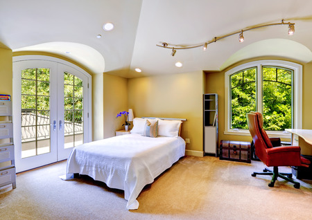 High vaulted ceiling bedroom with walkout deck. View of bed covered with white simple bedding, desk with whirlpool chair and antique chest photo
