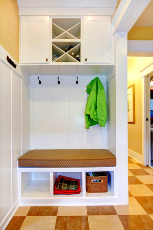 storage: White hallway storage cabinet with hangers, bench, three storage units under the bench and three section wine cabinet on the top