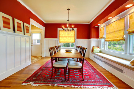 Red and white dining room with hardwood floor. View of table set and window bench with pillows Stok Fotoğraf