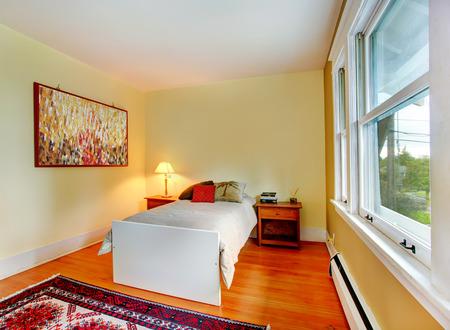 nightstands: Ivory wall rectangle bedroom with hardwood floor. View of single bed and nightstands Stock Photo