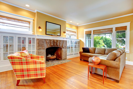 stone  fireplace: Gentle yellow living room with stone fireplace and built-in cabinets. View of big sofa and pleated antique chair Stock Photo
