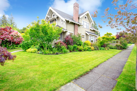 real estate house: House with tropical flower bed and lawn. View of walkway