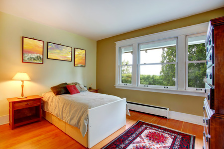 nightstands: Ivory wall rectangle bedroom with hardwood floor. View of single bed and nightstands. Room has big dresser