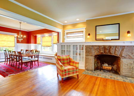 stone  fireplace: Gentle yellow living room with stone fireplace and built-in cabinets. View of red and white dining area