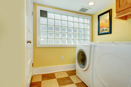 Yellow laundry room with washer, dryer and glass block window Stock Photo - 27593738