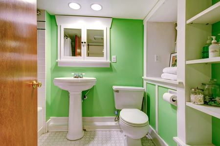 bathroom wall: Bathroom interior  Green wall blend perfeclty with white storage cabinet and white washbasin stand  with toilet