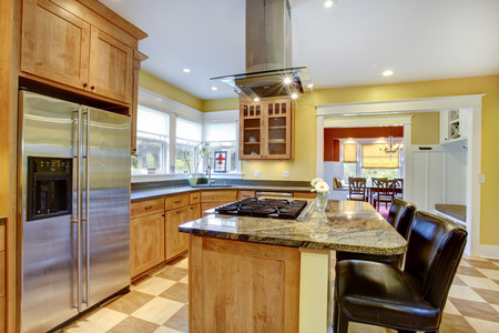 Yellow kitchen interior  View of island with built-in stove and kitchen hood above it photo