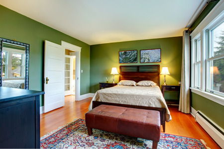 Green walls bedroom with high headboard bed, leather ottaman, black cabinet  and rug photo