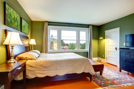 Green walls bedroom with high headboard bed, ottaman, black cabinet with tv, rug photo