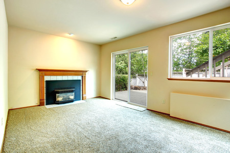 Empty room with fireplace and glass slide door to walkout deck photo