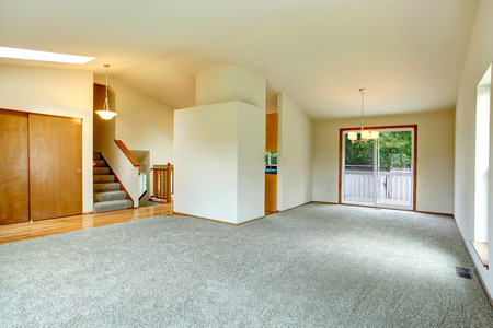 Spacious empty living room with walkout deck  Room has high vaulted ceiling and carpet floor  View of stairscase